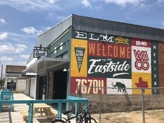 """Image of the restaurant Revival Eastside Eatery in Waco, TX. There is a colorful mural on the side of the building that says """"Welcome to the Eastside"""""""