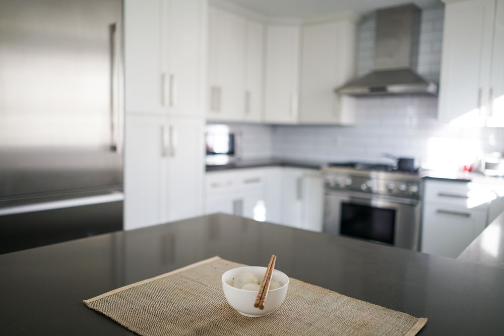quartz countertop with the white shaker cabinets and ...