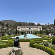 Photo of The Getty Villa - Pacific Palisades, CA, United States. The outside pool with Getty museum in background.