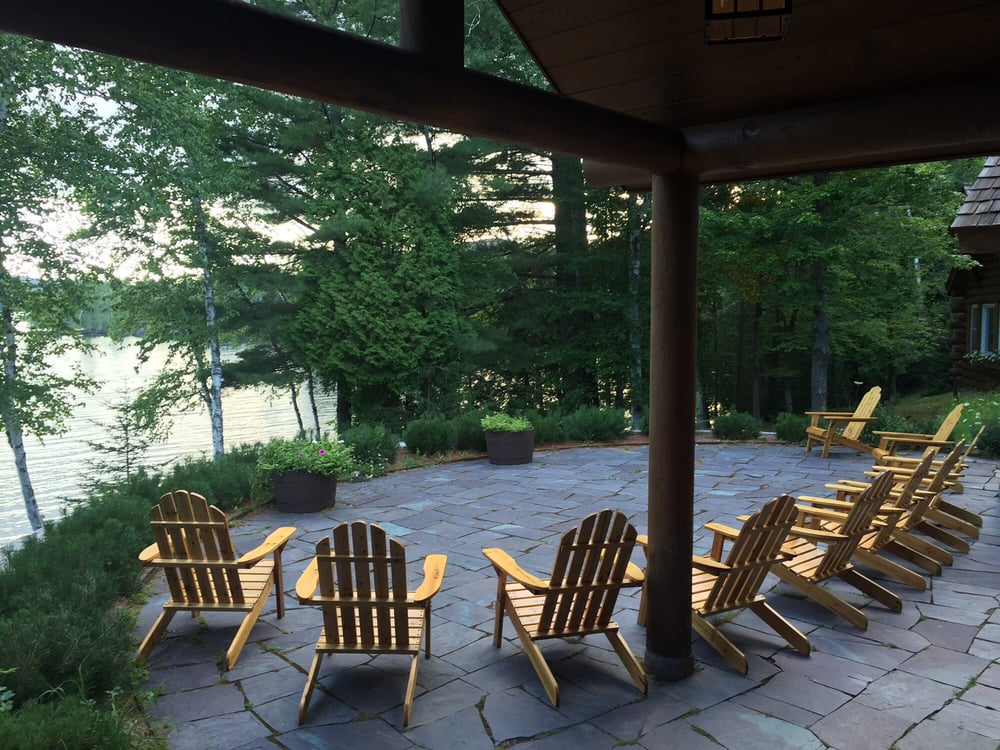 A tree-covered patio with Adirondack chairs