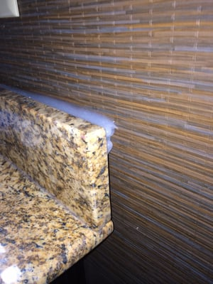 """Photo of Days Inn Downtown / at the Stadium - Nashville, TN, US. Bathroom counter top backsplash with about 3/4"""" gap where they tried to fill it in with caulk."""