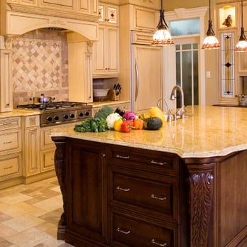 Large island in kitchen with stone countertop, carved wood ...